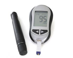 Glukometr wskazuje poziom cukru we kwrii w normie, obok leży nakłuwacz do palców
