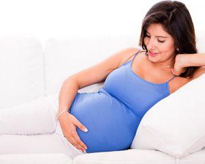 Ciężarna kobieta cierpiąca na cukrzycę ciążową odpoczywa na kanapie, trzymając się za brzuch